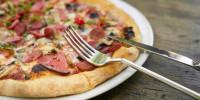 Besteck auf Teller mit frischer Pizza