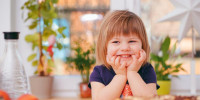 Lächelndes Kind, das das Kinn mit den Händen abstützt