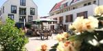 Blick auf den Dorfplatz durch Blumen und Pflanzen auf die Terrasse des Dorfcafé