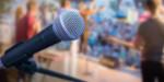 Symbolbild einer Veranstaltung mit einem Mikrophon und einer Band auf einer Bühne im Hintergrund