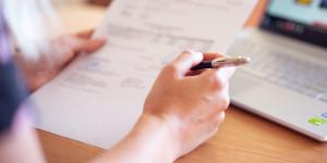 Hand mit Stift und Formular neben Laptop