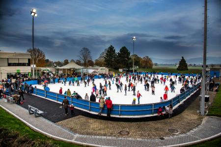 Eine große Eisbahn mit vielen Menschen, die Schlittschuhe fahren.